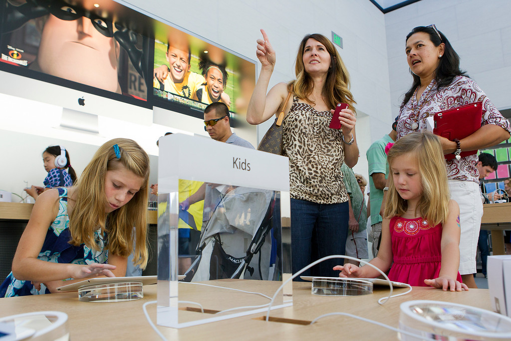 . Cecilia Cardenas, right, and Jennifer Krause, center, check out the redesigned Apple Store at the Stanford Shopping Center as Krause\'s children Hannah Krause, 7, left, and Natalie Krause, 4, (right) play with iPads, in Palo Alto, Calif., on Saturday, Sept. 7, 2013.  (LiPo Ching/Bay Area News Group)