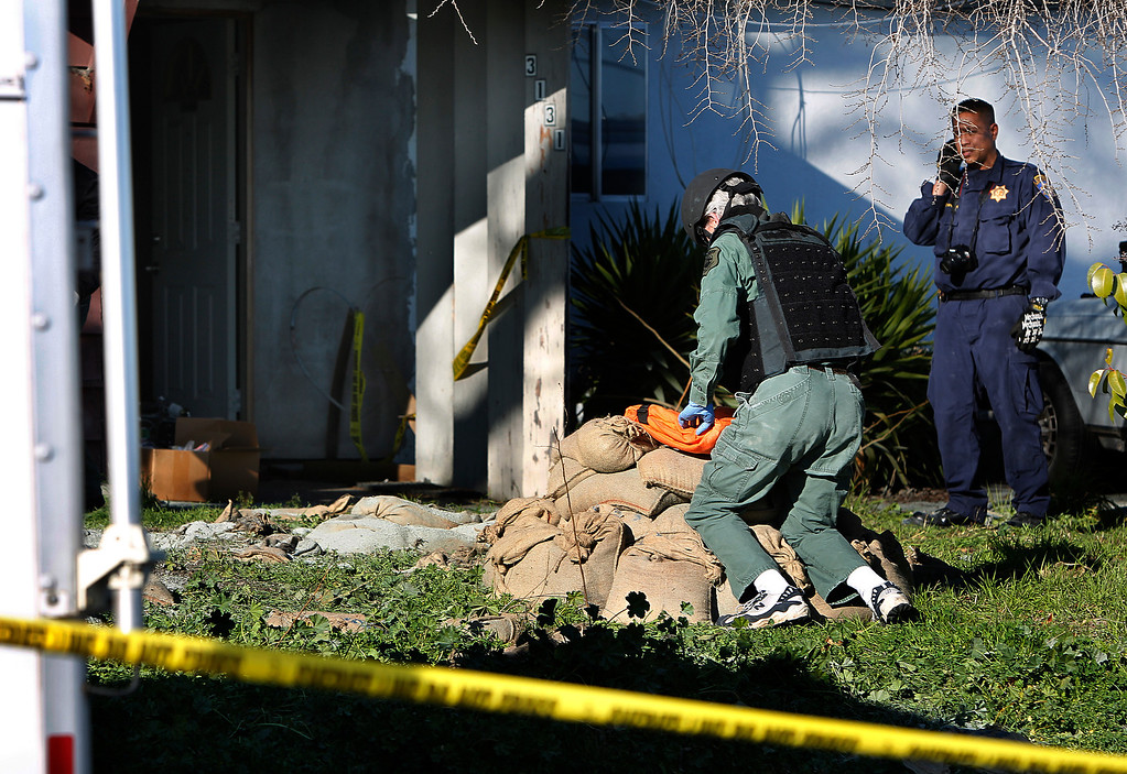. A Santa Clara County Sheriff\'s Bomb Squad officer packs up materials at sandbags in front of Everett Basham\'s house on Humbolt Ave., in Santa Clara, Calif. on Wednesday, Feb. 13, 2013.  Originally, law enforcement officers planned to detonate destructive devices found at Basham\'s house in the sandbags, but decided to detonate them in a contained environment the next day. (LiPo Ching/Staff)
