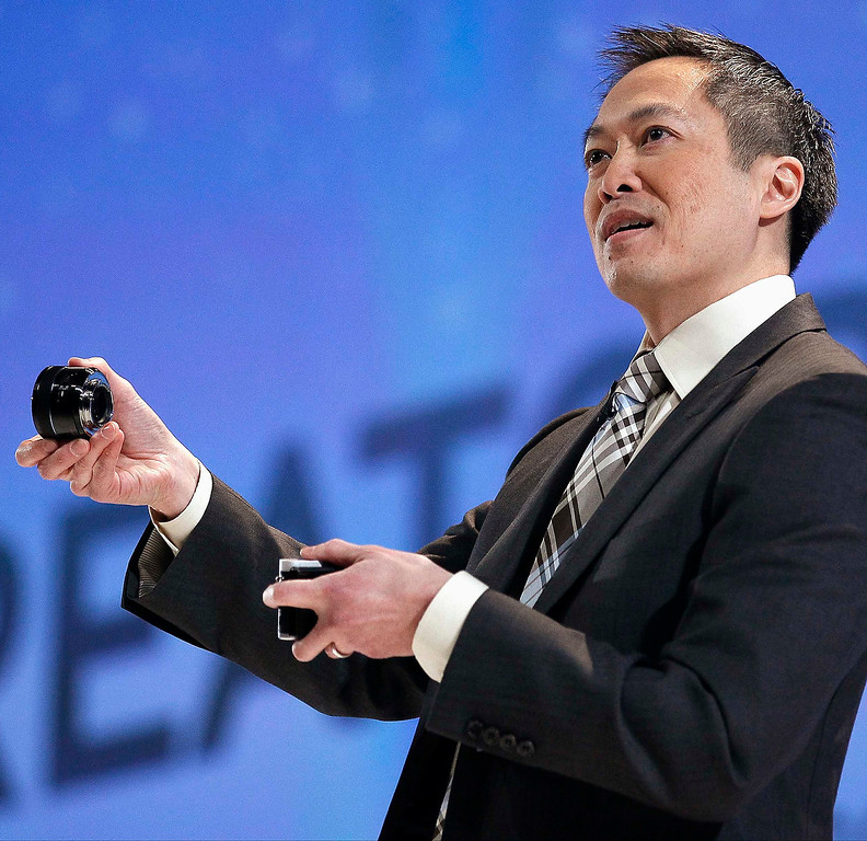 . Michael Abary, senior vice-president for Samsung Electronics America, shows off a new 45mm F/1.8 lens for the NX300 camera, describing it as the world\'s first single-lens 3D system, at the Samsung news conference at the Consumer Electronics Show (CES) in Las Vegas January 7, 2013. (REUTERS/Rick Wilking)