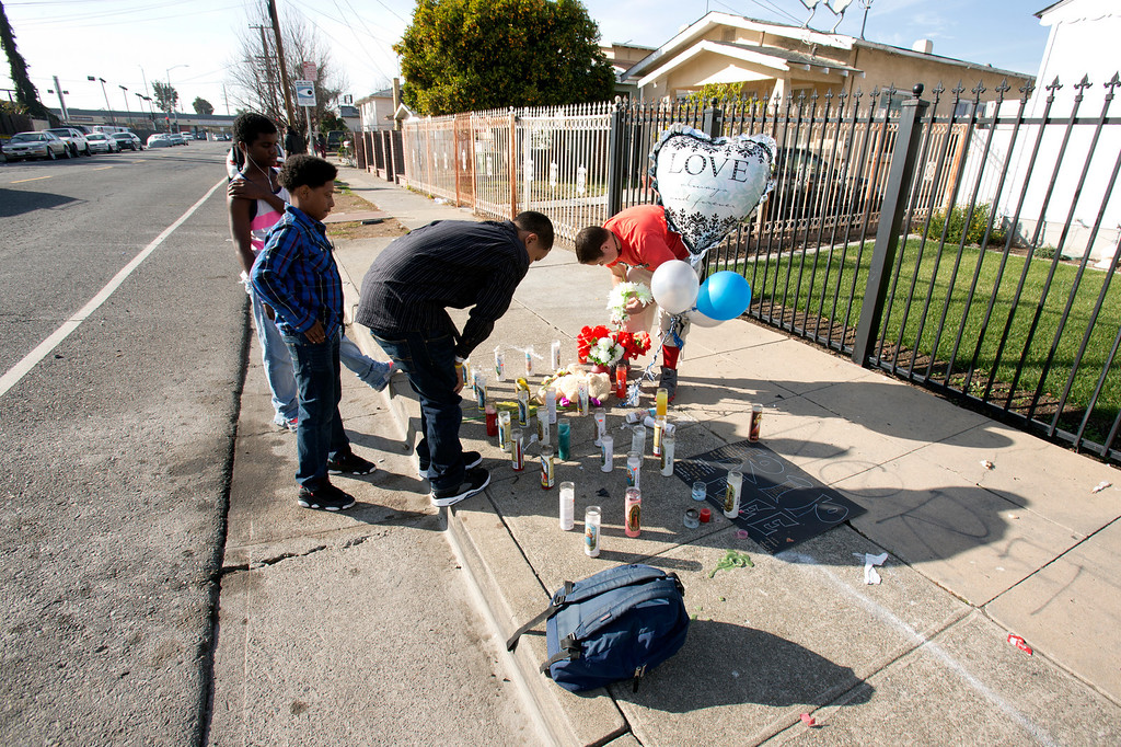 . Schoolmates pause at a street memorial for Lee Weathersby III, the 13-year-old boy who was shot dead while coming home from the Boys and Girls Club on New Year\'s Eve, Thursday, Jan. 2, 2014 in Oakland, Calif. (D. Ross Cameron/Bay Area News Group)