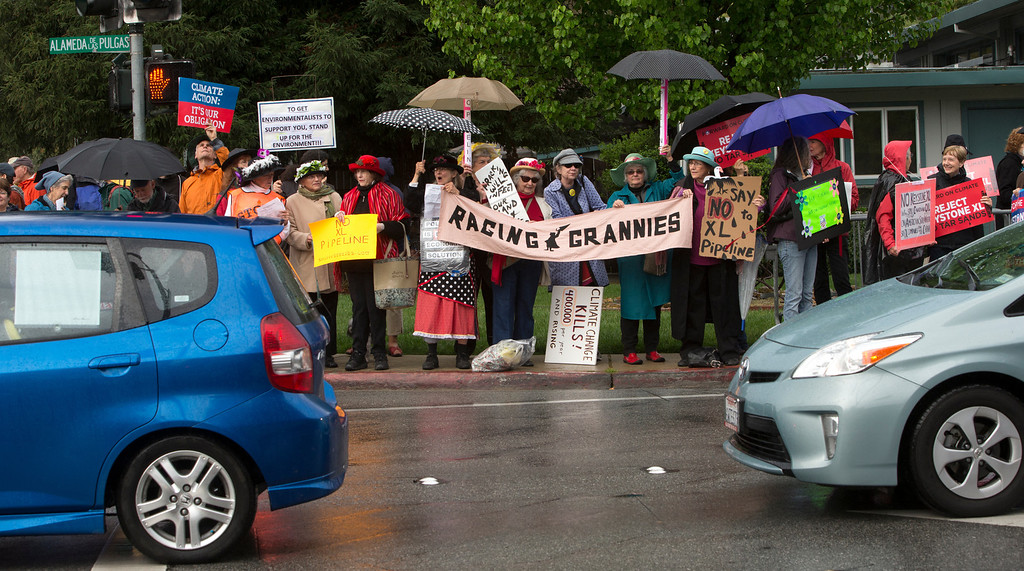 . Protesters line up along Alameda de las Pulgas as they wait for President Obama\'s motorcade to pass en route to a fundraising event in Atherton, Calif., on Thursday, April 4, 2013. (John Green/Staff)