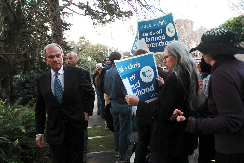 """. A guest to a campaign fundraiser for New Jersey Republican Gov. Chris Christie walks past protesters standing in front of the home of Facebook CEO Mark Zukerberg in Palo Alto on Wednesday, Feb. 13, 2013. About 40 protesters rallied in front of the home, saying they objected to Christie�s visit because of his efforts to strip funding from Planned Parenthood and other women�s reproductive health care programs. Protester and Palo Alto resident Cheryl Lilienstein said she wondered whether Zuckerberg had any idea what Planned Parenthood means for women\'s health or what Christie�s stances are. \""""I hope he\'s just confused,\"""" she said. Zuckerberg and wife Priscilla Chan first got to know Christie after donating $100 million to struggling Newark, N.J., schools two years ago, according to a Facebook spokeswoman.   (Kirstina Sangsahachart/ Daily News)"""