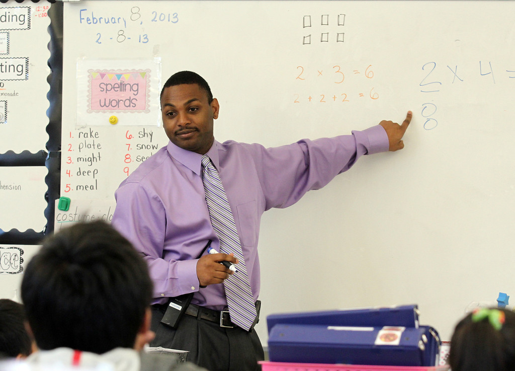 . Principal Jawan Eldridge does some multiplication problems with the second grade class at Peres Elementary School in Richmond, Calif., on Friday, Feb. 8, 2013.  Peres school is one of two elementary schools in Richmond that have raised their average API test scores to over 800. (Laura A. Oda/Staff)