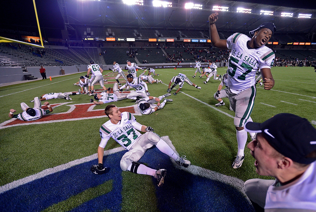 . De La Salle Spartan players perform a ritual slide into the end zone as they celebrate their win over the Centennial Huskies in the Open Division during the 2012 CIF State Football Championship at Home Depot Center in Carson , Calif. on Saturday, Dec. 15, 2012. De La Salle defeated Centennial 48-28. (Jose Carlos Fajardo/Staff)