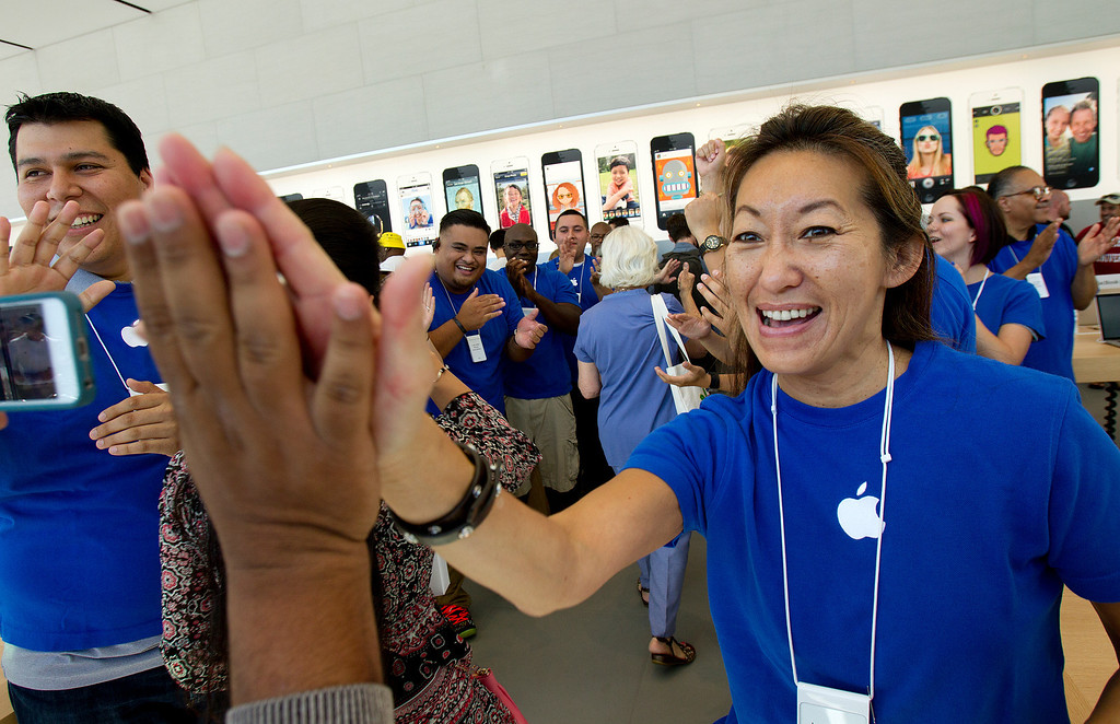 . Apple Business Specialist Mary Rye, right, greets customers at the redesigned Apple Store at the Stanford Shopping Center in Palo Alto, Calif., on Saturday, Sept. 7, 2013.  (LiPo Ching/Bay Area News Group)
