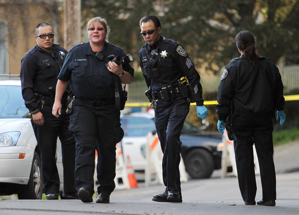 . Oakland police and police crime scene technicians investigate near Dimond Park as a man was found dead of gunshot wounds on Canon Avenue in Oakland, Calif. on Friday, Jan. 11, 2013.  (Jane Tyska/Staff)
