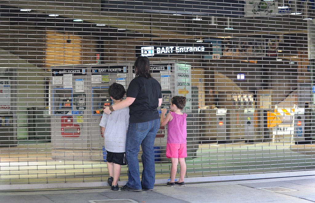 . Amber Greene, center, and her children, Hunter, 7, left, and Kelly, 5, right, of Oakhurst,  stand at the closed gates to the Dublin-Pleasanton BART station in Pleasanton, Calif. on Tuesday, July 2, 2013. Greene had hoped to take her kids to San Francisco on her day off from working at the Alameda County Fair. BART is in the second day of a strike. (Dan Honda/Bay Area News Group)