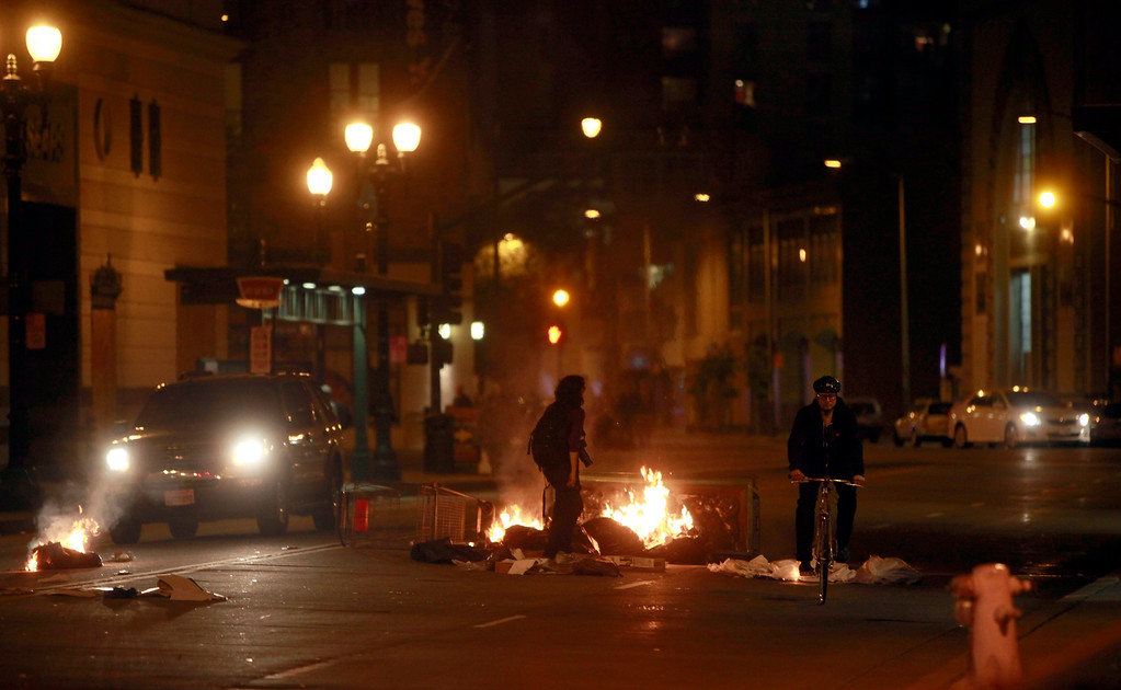 . A garbage fire burns on 20th Street on the third day of protests over the acquittal of George Zimmerman Monday evening, July 15, 2013 in Oakland, Calif. (Karl Mondon/Bay Area News Group)