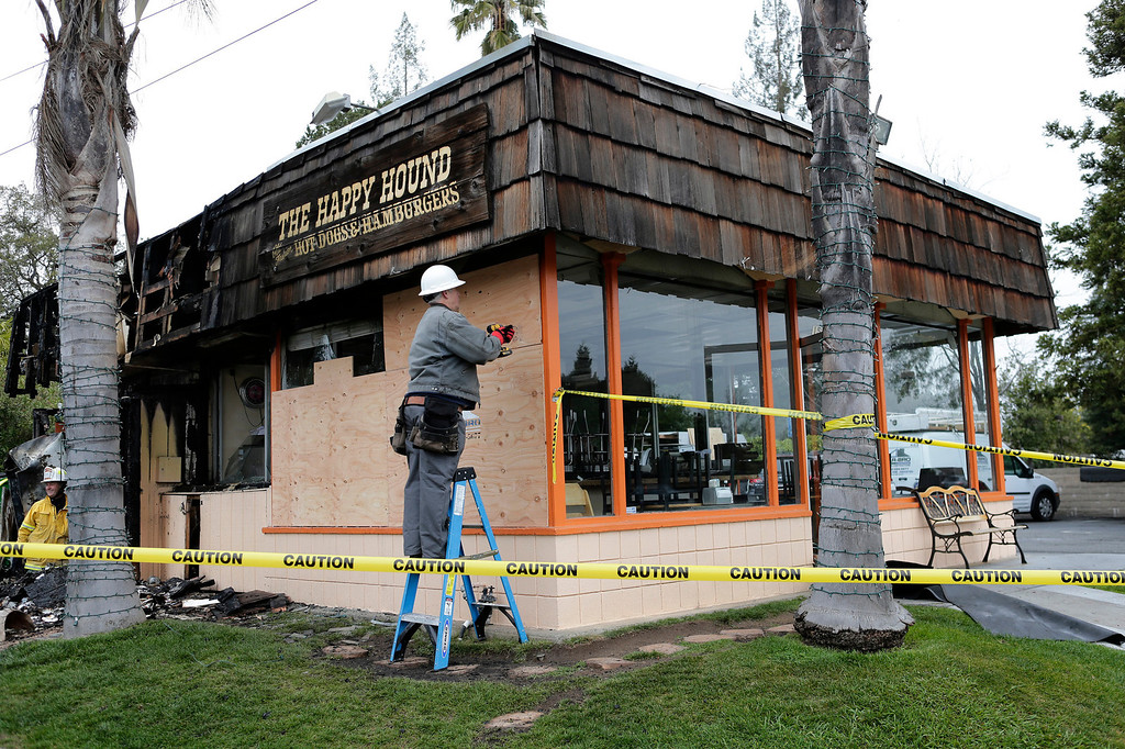 . A worker boards up the windows at the Happy Hound restaurant in Los Gatos, Calif. following an early morning fire on Monday, March 4, 2013. The family owned restaurant has been a Los Gatos landmark for over forty years. (Gary Reyes/ Staff)