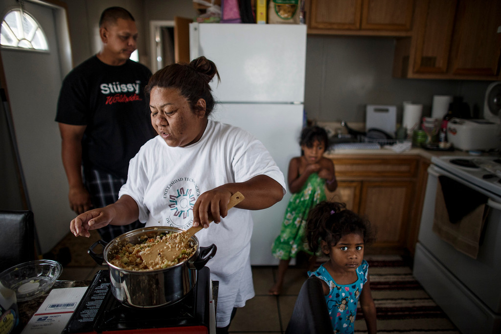 . Clarissa Taitano prepares fried rice as her daughters, A\'Riyah Jackson, 5, in green dress, and I\'Yannah Jackson, 3, and her partner, Mike Finona spent time in the kitchen area of their mobile home on May 24, 2013, in San Jose. The family recently moved to their mobile home after living in a Santa Clara motel for 64 days. (Dai Sugano/Bay Area News Group)
