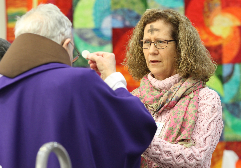 . Father Larry Dunphy, O.F.M. gives Chaplain Dorothy Chaknova communion during the Ash Wednesday Mass at the Mercy Retirement & Care Center in Oakland, Calif. on Wednesday, Feb. 13, 2013.  Father Larry, a Franciscan Priest,  comes to the Senior Care Center to deliver Mass for the many seniors who are unable to travel outside of the center.  Mass is delivered every Sunday at the center where the average age is 91 years old and 90% of the residents are catholic.  During Lent, they will have Stations of the Cross prayer service every Friday at 2:00 pm. (Laura A. Oda/Staff)