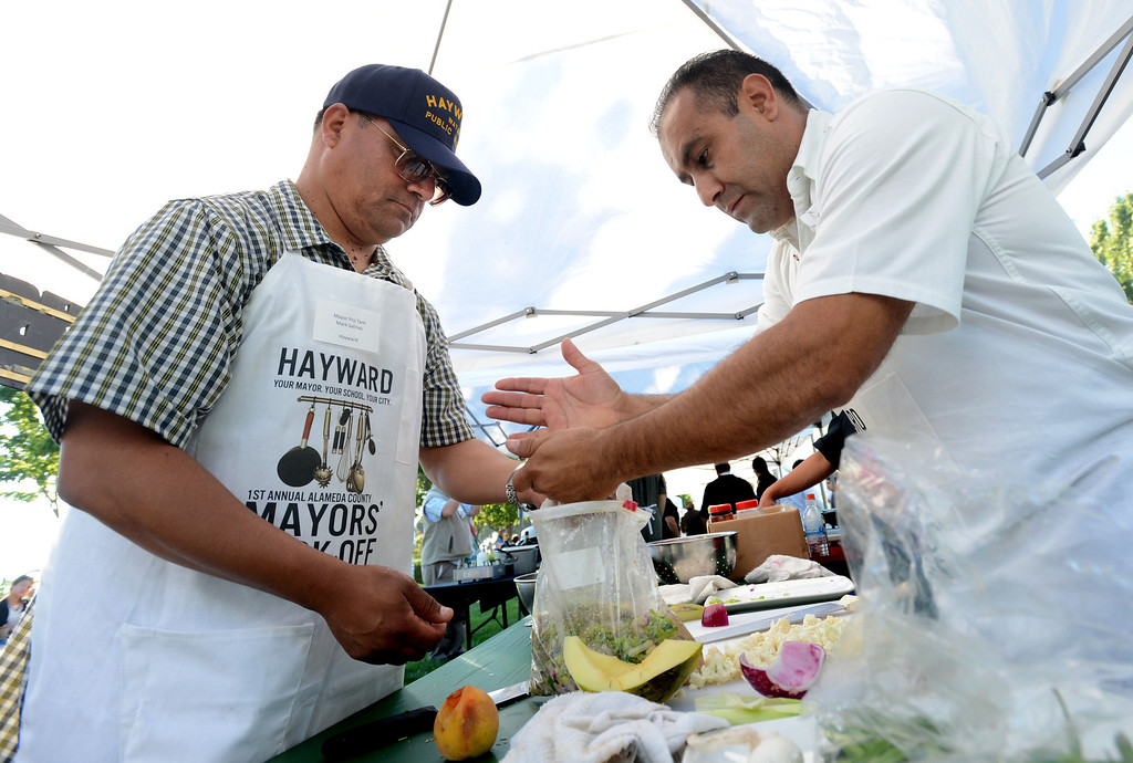 """. Hayward Mayor Pro Tem Mark Salinas, left, and Chef Tony Solorio with the Hayward\'s Tacos Uruapan restaurant prepare a chicken marinade during the \""""Alameda County Mayors\' Healthy Cook-Off Challenge\"""" held at the Dublin Farmers\' Market at Emerald Glen Park in Dublin, Calif., on Thursday, July 25, 2013. The Hayward team went on to place second, advancing them to compete against the winners of the Contra Cost County Mayors\' Healthy Cook-Off Challenge. The contest will be held at Mt. Diablo High School in the fall. The cook-off was presented by Concord\'s Wellness City Challenge and promotes the importance of healthy eating. (Doug Duran/Bay Area News Group)"""