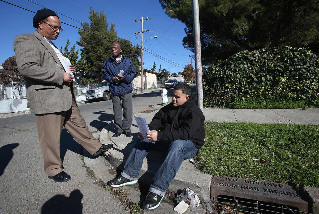 . Donald Paul Miller, left, and Ben Darden, center, of Allen Temple Baptist Church, talk with Alberto, 19, after praying at a homicide scene on 94th Avenue and Hillside Street in Oakland, Calif. on Saturday, Jan. 12, 2013. Miller, Darden, and others do community outreach immediately after homicides in Oakland. Ken Harbin, 17, who lived nearby, was shot and killed there on Friday night about 8:15 p.m. according to Oakland police. Harbin was a friend of Alfredo. There were four homicides in six hours on Friday in Oakland.  (Jane Tyska/Staff)