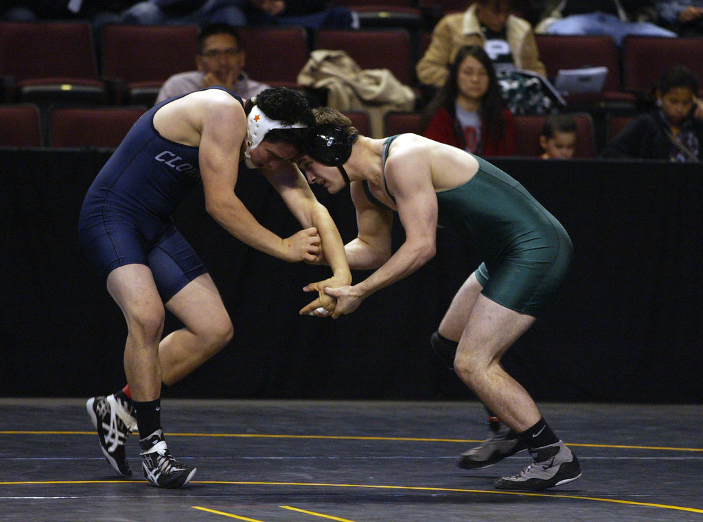 . De La Salle\'s Aaron Pease, left, wrestles Clovis East\'s Nick Callender in a 170-pound match during the California Interscholastic Federation wrestling championships in Bakersfield, Calif., on Friday, March 1, 2013. Pease would go on to win the match. (Anda Chu/Staff)