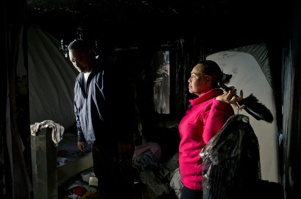 . At right, Anna Paasi holds clothes she found as her husband Uatesoni Paasi looks around the bedroom of their house that was destroyed by a fire in December, in San Mateo, Calif. on Thursday, Jan. 2, 2014.  (LiPo Ching/Bay Area News Group)
