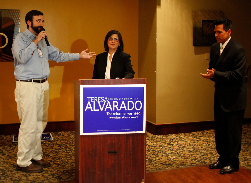 . Communications director Peter Allen, on left, introduces Santa Clara County Board of Supervisors candidate Teresa Alvarado, center, with husband Jess Moreles, on right,  at Flames Restaurant in downtown San Jose, Calif., Tuesday, July 30, 2013. (Josie Lepe/Bay Area News Group)