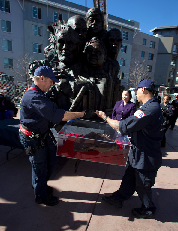 ". Oakland firefighters carry a piece of steel from the twin towers of the World Trade Center, to be placed inside Mario Chiodo\'s ""Remember Them\"" statue, at a ceremony to dedicate the final section of Chiodo\'s paean to heroes of civil rights and humanity, Thursday, Feb. 21, 2013 in Oakland Calif. (D. Ross Cameron/Staff)"