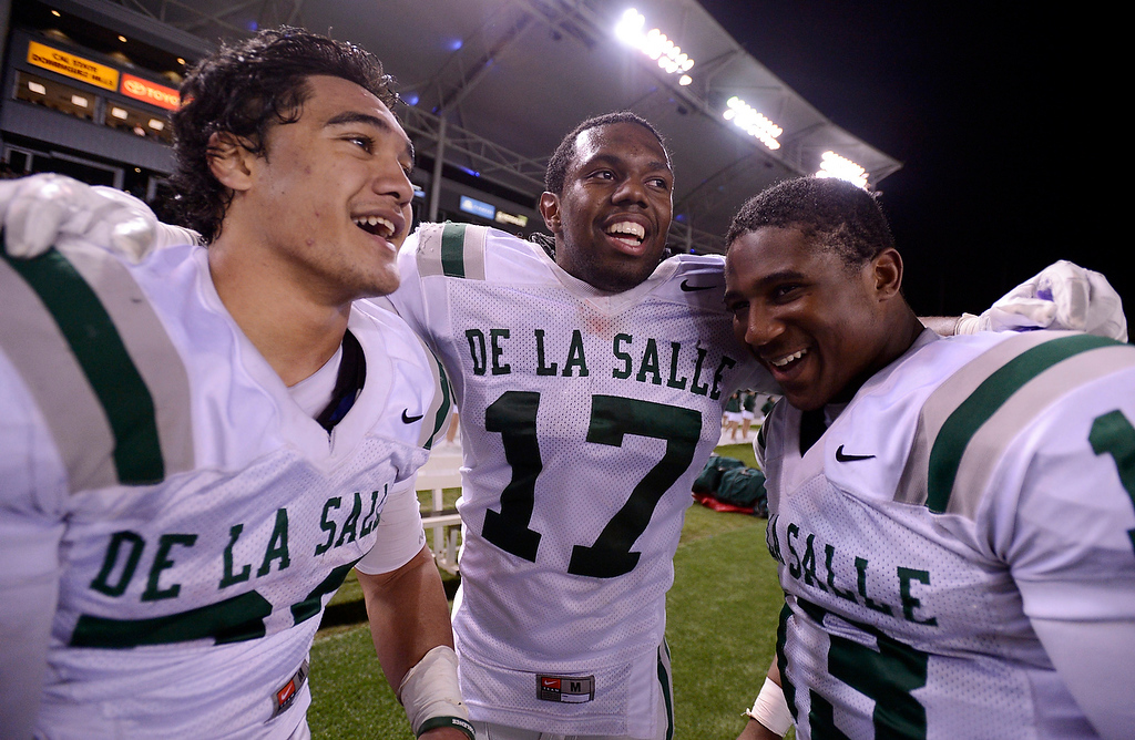 . De La Salle Spartans\' Tiapepe Vitale (20), Michael Hutchings (17) and Chris Williams (13) celebrate their win in the final minute of the fourth quarter against the Centennial Huskies in the Open Division during the 2012 CIF State Football Championship at Home Depot Center in Carson , Calif. on Saturday, Dec. 15, 2012. De La Salle defeated Centennial 48-28. (Jose Carlos Fajardo/Staff)