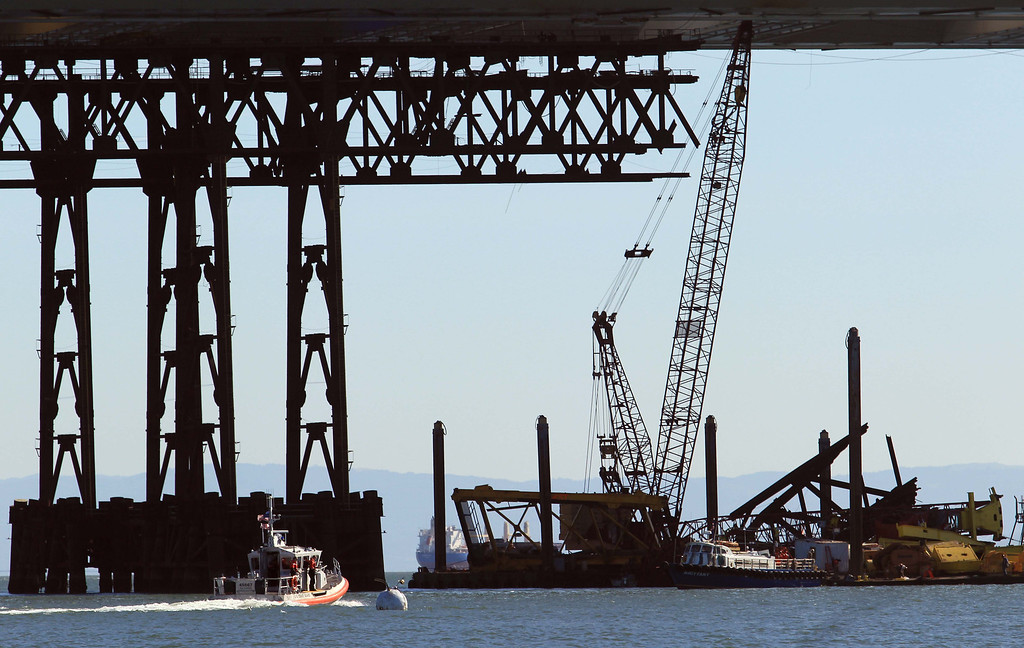. A Coast Guard boat, left, heads to the scene after a barge crane, right, collapsed while removing iron falsework from the new Oakland-San Francisco Bay Bridge project in San Francisco, Calif. on Thursday, Feb. 21, 2013. No one was injured in the incident. (Jane Tyska/Staff)