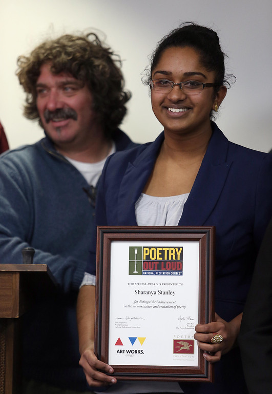 . First-place winner Sharanya Stanley, of Dublin High School, receives her award during the Poetry Out Loud competition at the Alameda County Lakeside Plaza Building in Oakland, Calif., on Wednesday, Feb. 13, 2013. To the left is Andrew Johnson, prompter and professional artist. (Jane Tyska/Staff)