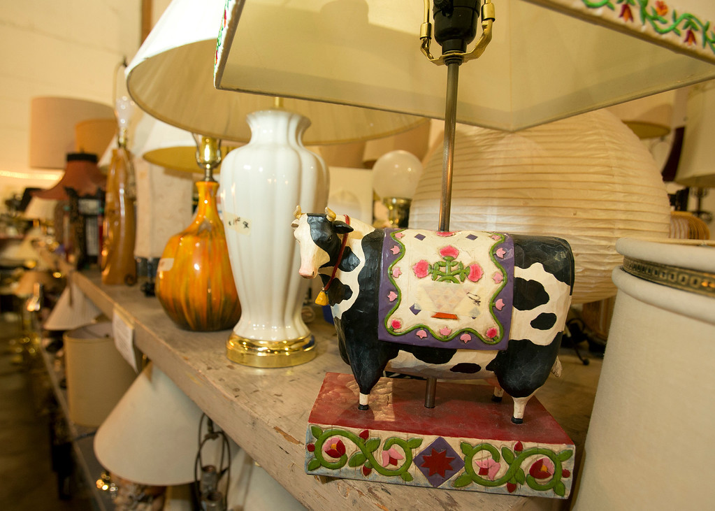 . All manner of table lamps -- even ones with a Holstein cow for a base -- are available at the annual White Elephant Sale, at the Oakland Museum Women\'s Board 96,000-square-foot warehouse in Oakland, Calif., Tuesday, Jan. 15, 2013. (D. Ross Cameron/Staff)