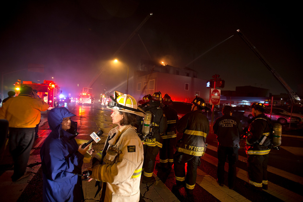 . Television journalists interview an Oakland Fire Captain outside the site of a house fire on Harrison Street near 7th Street, Wednesday, Jan. 23, 2013 in Oakland, Calif. The building, which fire investigators said was built in 1896, caught fire when squatters inside it tried to cook food over an open flame. (D. Ross Cameron/Staff)