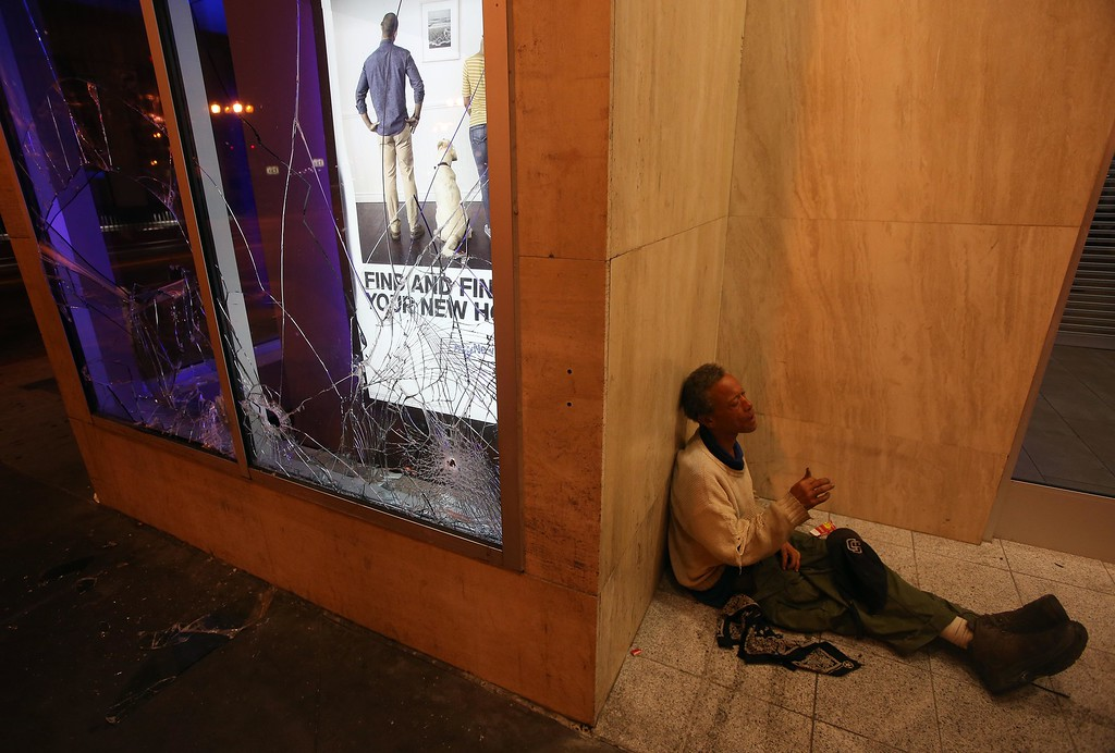 . A street person sits next to a smashed window at the Chase Bank on Broadway and 14th Street in downtown Oakland, Calif., early Sunday, July 14, 2013. Protesters also lit several small fires on Telegraph Avenue and sprayed graffiti after learning that George Zimmerman had been found not guilty in the shooting death of Trayvon Martin in Sanford, Fla. (Jane Tyska/Bay Area News Group)