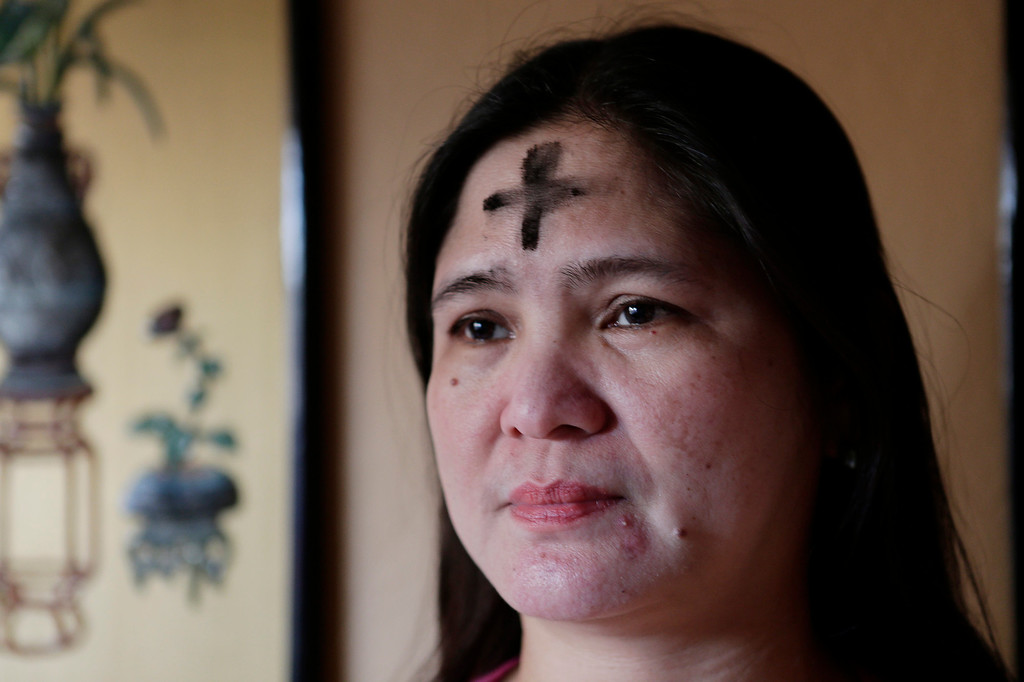 . Josie Prado shows the ash sign of the cross on her forehead applied by Rev. Michael Gazzingan on Ash Wednesday in San Jose, Calif. on Wednesday, Feb. 13, 2013. Prado works as a caregiver for patients at Merienneth Villa. Ash Wednesday marks the first day of Lent. Ashes are placed on the foreheads of Christians in the sign of the cross as a sign of mourning and repentance.  (Gary Reyes/ Staff)