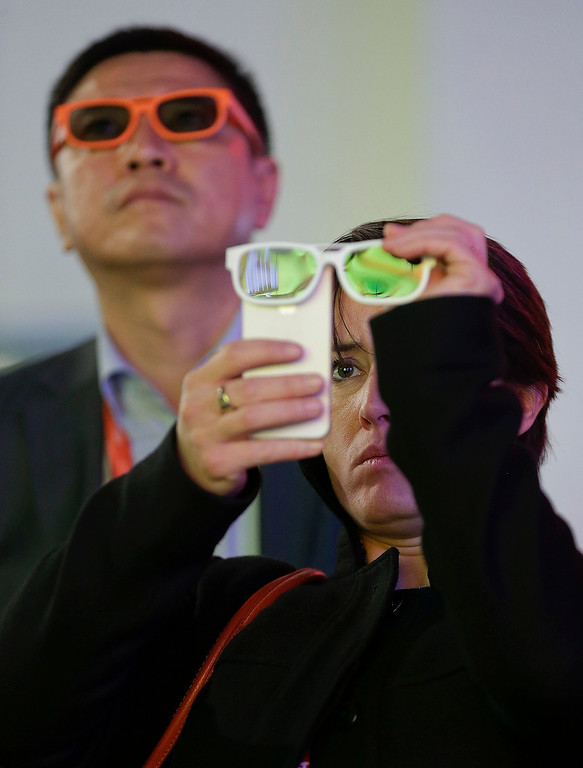 . Buyer Julie Carpenter records 3-D video with her iPhone through a pair of 3-D glasses at the Consumer Electronics Show, Thursday, Jan. 10, 2013, in Las Vegas. (AP Photo/Julie Jacobson)