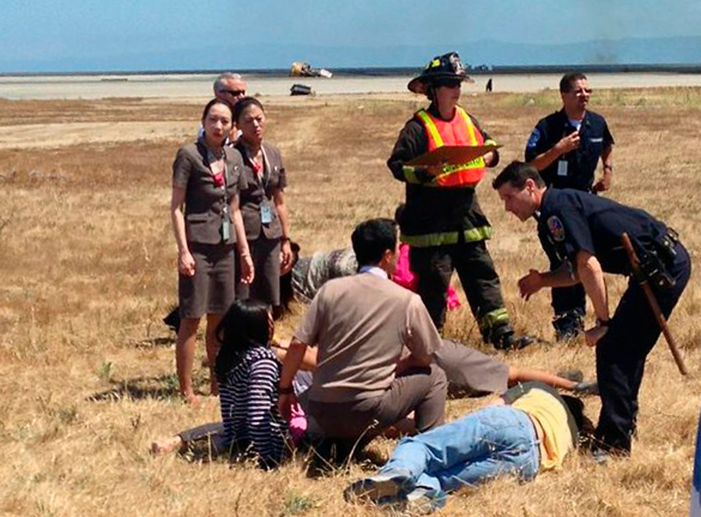. Asiana Airlines flight attendant Kim Ji-yeon, left, stands near a runway with rescued passengers after flight 214 crash landed at San Francisco International Airport on July 6, 2013, in this handout photo provided by passenger Eugene Anthony Rah released to Reuters on July 8, 2013.  (Eugene Anthony Rah via Reuters)