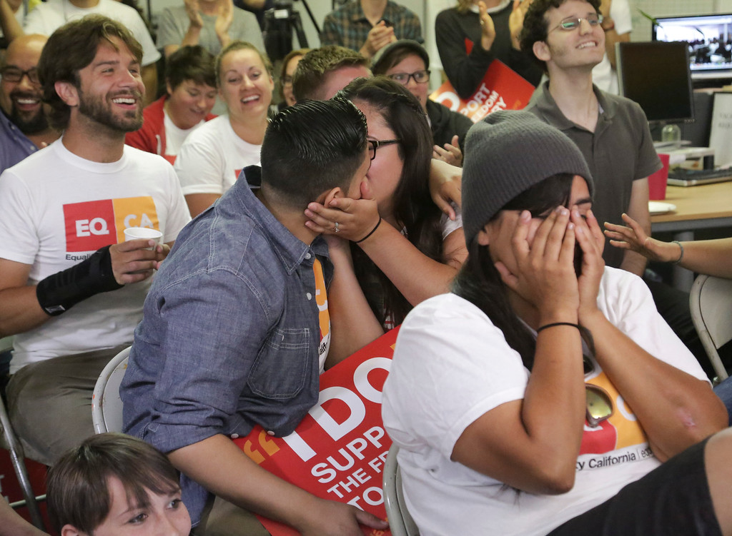 . Domestic partners Alicia Guajardo, left, and Isabella Restrepo, both 24 of Los Angeles, kiss after the Supreme Court ruling on the Defense of Marriage Act at the offices of Equity California, the state\'s largest gay rights group, in West Hollywood, Calif., Wednesday, June 26, 2013.  The justices issued two 5-4 rulings in their final session of the term. One decision wiped away part of a federal anti-gay marriage law that has kept legally married same-sex couples from receiving tax, health and pension benefits. The other was a technical legal ruling that said nothing at all about same-sex marriage, but left in place a trial court\'s declaration that California\'s Proposition 8 is unconstitutional.  (AP Photo/Jason Redmond)