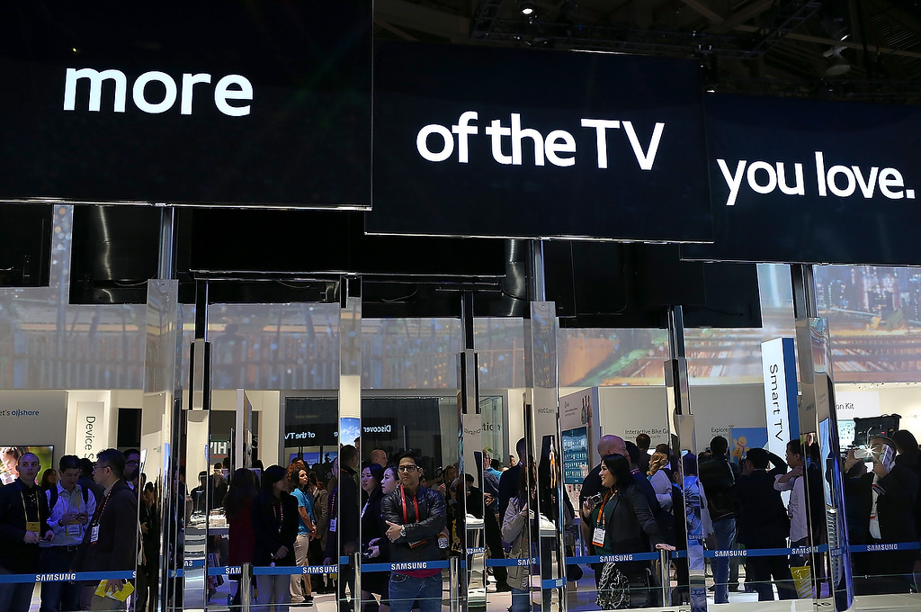 . Attendees look at a display of Samsung televisions during the 2013 International CES at the Las Vegas Convention Center on January 8, 2013 in Las Vegas, Nevada. (Photo by Justin Sullivan/Getty Images)