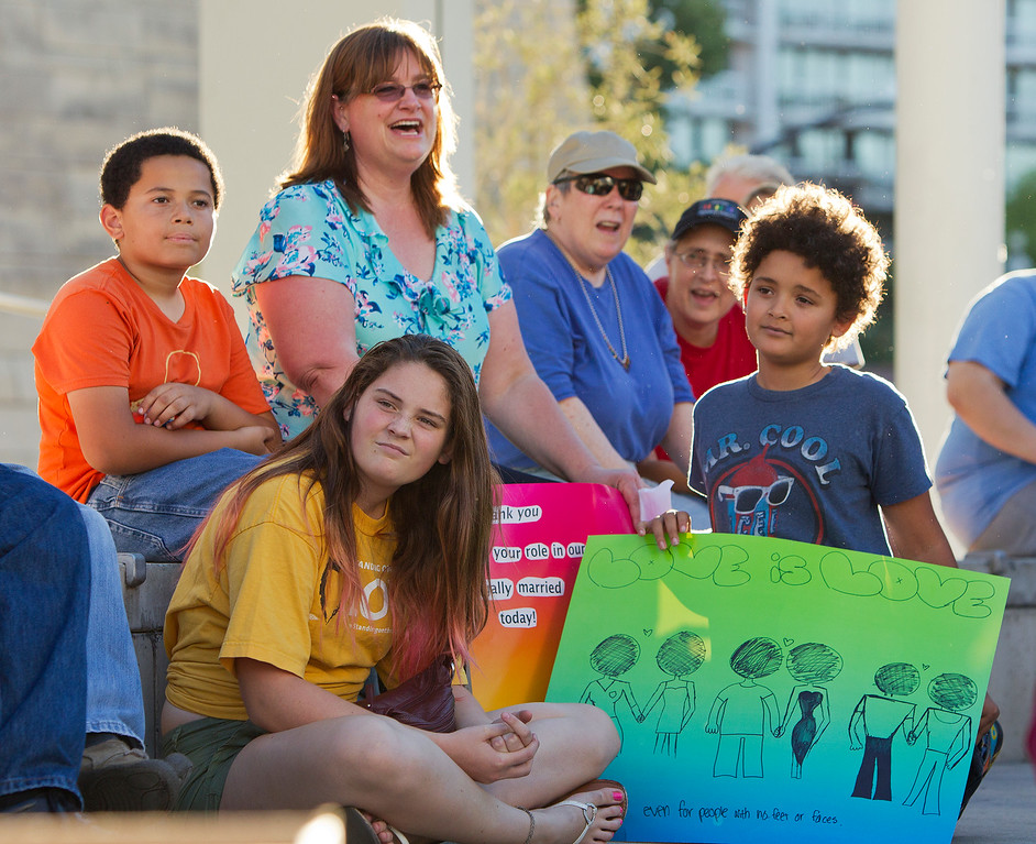 . At center left in the background, Kristin Rivers, Ph.d. is surrounded by her children, from left, Miles Rivers, Elara Rivers and Johnny Rivers at a San Jose City Hall rally to celebrate the U.S. Supreme Court decision on DOMA and Proposition 8, in San Jose, Calif. on Wednesday, June 26, 2013. (LiPo Ching/Bay Area News Group)