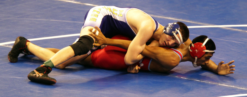 . Gilroy\'s Paul Fox, left, wrestles Santa Ana\'s Gil Gutierrez in a 132-pound second round match during the California Interscholastic Federation wrestling championships in Bakersfield, Calif., on Friday, March 1, 2013. Fox would go on to win. (Anda Chu/Staff)