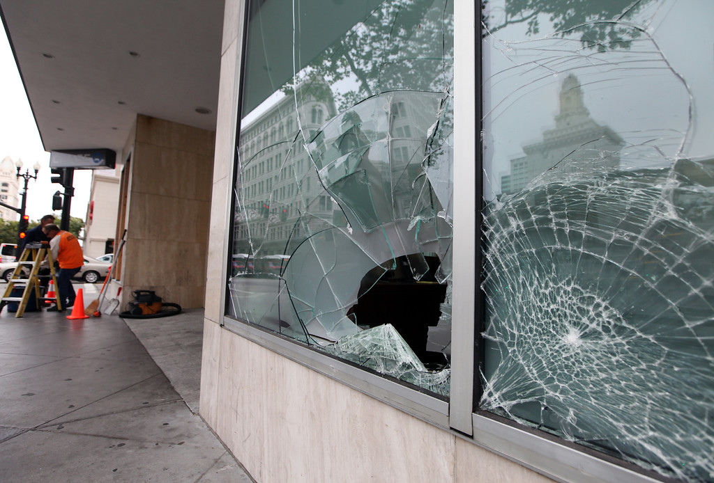 . Workers begin the process of boarding up the broken windows at Chase  Bank on Broadway in Oakland, Calif., Monday, July 15, 2013.  Downtown Oakland merchants are once again cleaning up after a weekend of protest and late night violence. (Laura A. Oda/Bay Area News Group)