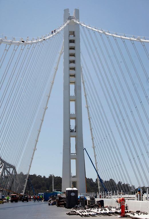 . Two tiny figures climb high on the cable of the Bay Bridge toward the top of the single anchor suspension tower Thursday afternoon May 23, 2013 in San Francisco, Calif. The tower is comprise of four legs with shear links designed to take the energy of an earthquake and spare the tower major damage. (Karl Mondon/Bay Area News Group)