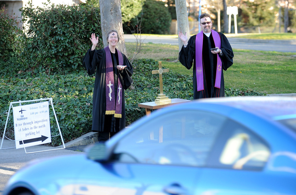 . The Rev. Christy Parks-Ramage, left, with the First Congregational Church of Antioch, and The Rev. Will McGarvey, with the Community Presbyterian Church of Pittsburg, wave to a passing motorist during the drive-by prayers and the imposition of ashes for Ash Wednesday held in Pittsburg, Calif., on Wednesday, Feb. 13, 2013. The drive-through Ash Wednesday was held by the East County Shared Ministry. (Doug Duran/Staff)