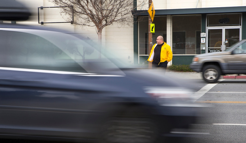 . A car whizzes past Redwood City police community service officer Steve Diaz while in the crosswalk on El Camino Real in Redwood City, Calif., on Wednesday, March 20, 2013. Diaz was part of a county wide program invoving 25 officers from 16 different agencies targeting drivers not stopping for pedestrians in the cross walk and excessive speed. About 200 citations were handed out on Wednesday. (John Green/Staff)