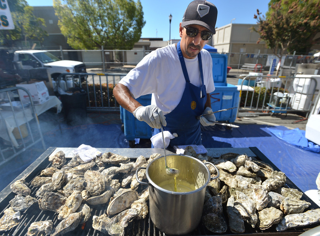 . Sergio Castro, of Pittsburg, prepares to put a butter sauce on  barbecue oysters at the 29th annual Pittsburg Seafood and Music Festival in the city\'s historic Old Town in Pittsburg, Calif., on Saturday, Sept. 7, 2013. (Dan Rosenstrauch/Bay Area News Group)