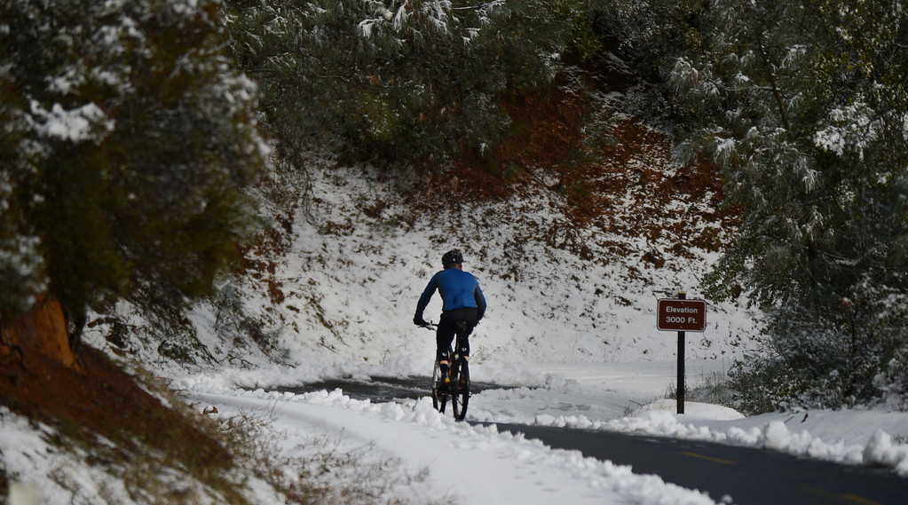 . A brave bicyclist rides past the 3,000 feet elevation marker at Mount Diablo State Park in Walnut Creek, Calif., on Tuesday, Feb. 19, 2013. Many came to the park to enjoy the winter wonderland and hiked up the closed road to be in the snow. (Susan Tripp Pollard/Staff)