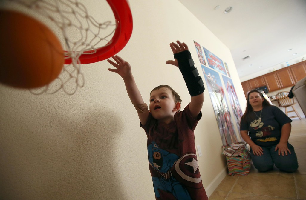 . Matthew Ouimet, 3, shoots baskets as his mom Kristi, right, watches at their home in Antioch, Calif., on Thursday, May 22, 2014. (Jane Tyska/Bay Area News Group)