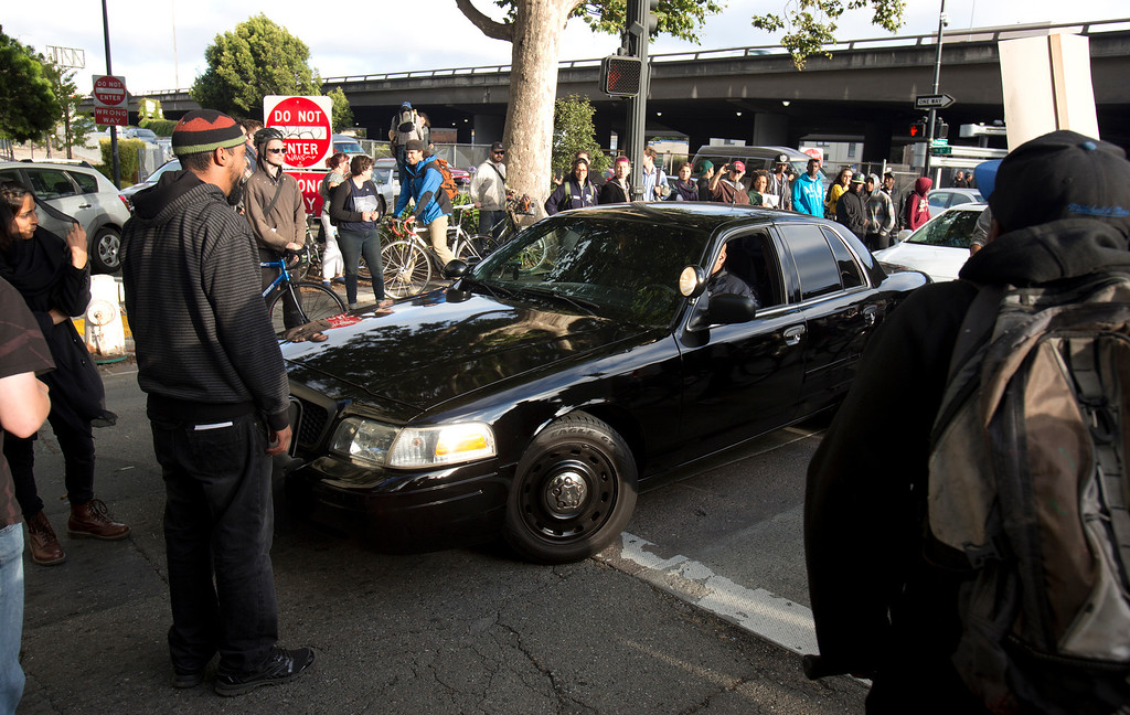 . Protesters block an unmarked police car on Broadway during a protest of the verdict in the Trayvon Martin murder trial last Saturday in Sanford, Fla., Monday, July 15, 2013 in Oakland, Calif. (D. Ross Cameron/Bay Area News Group)