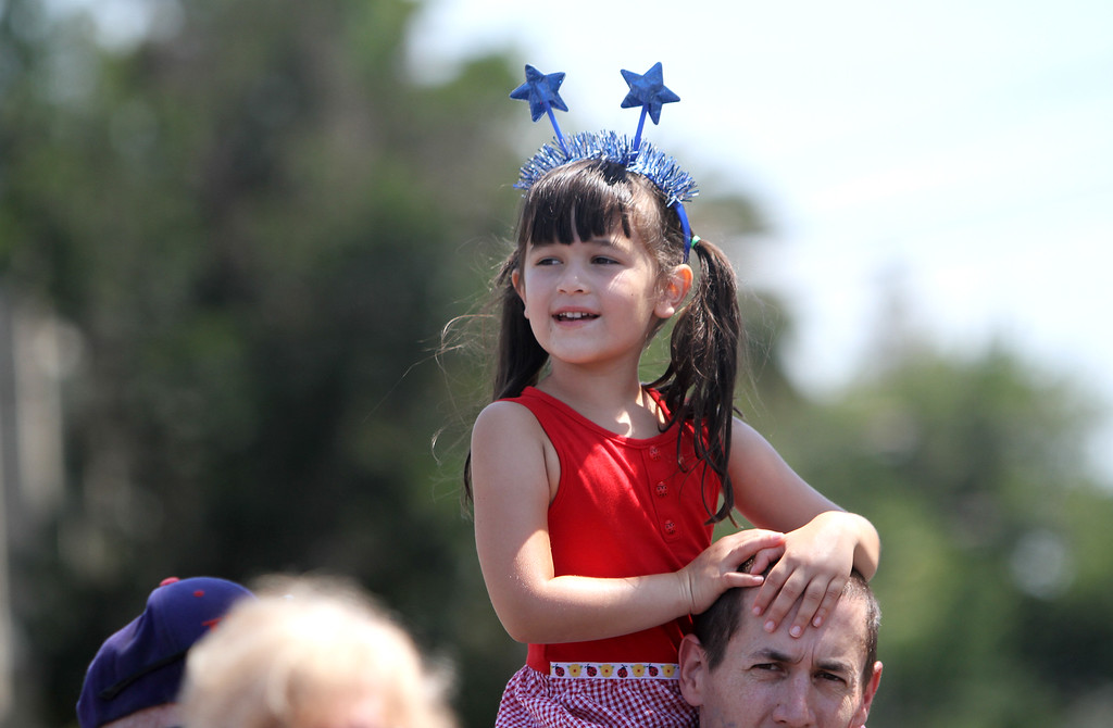 . Vivian Pedicord, 6, of Redwood City sits on her dad\'s shoulders on Arguello Street to watch Redwood City\'s 75th annual Fourth of July Parade on Thursday, July 4, 2013. (Kirstina Sangsahachart/ Daily News)