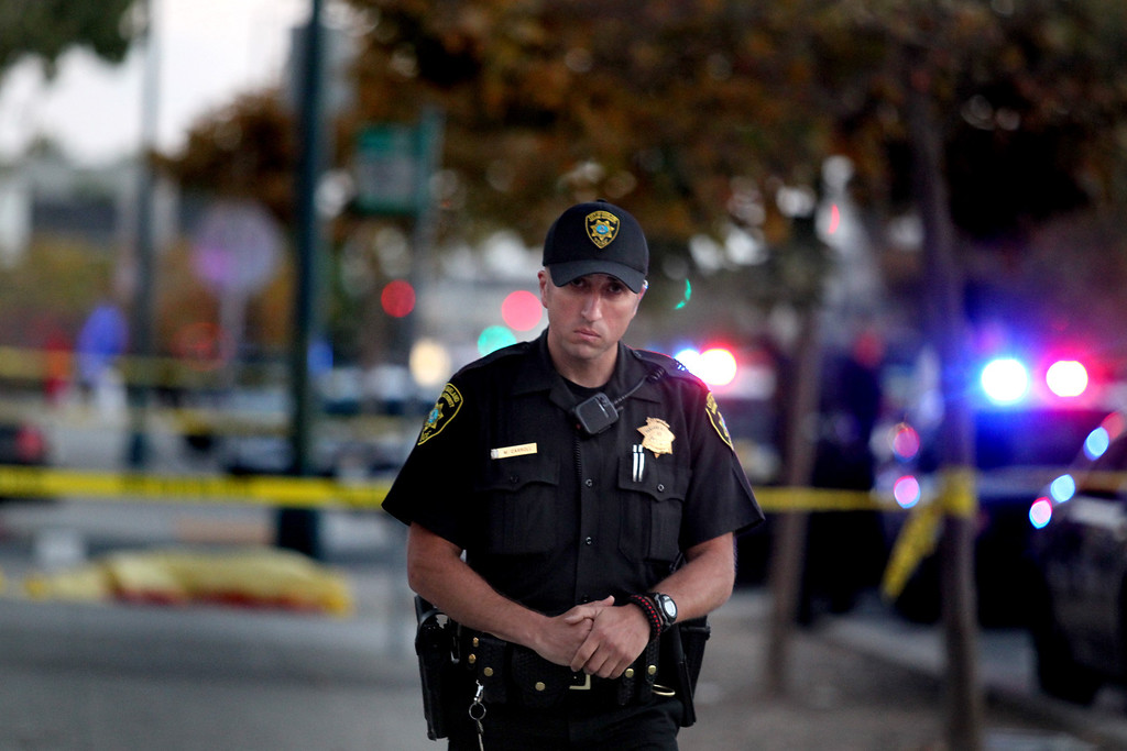 . An officer from the Oakland Housing Authority Police Department stands guard at the crime scene as the Oakland police investigate the 58th homicide at Mandela Parkway and 10th Street in Oakland, Calif., on Friday, Aug. 2, 2013. (Ray Chavez/Bay Area News Group)