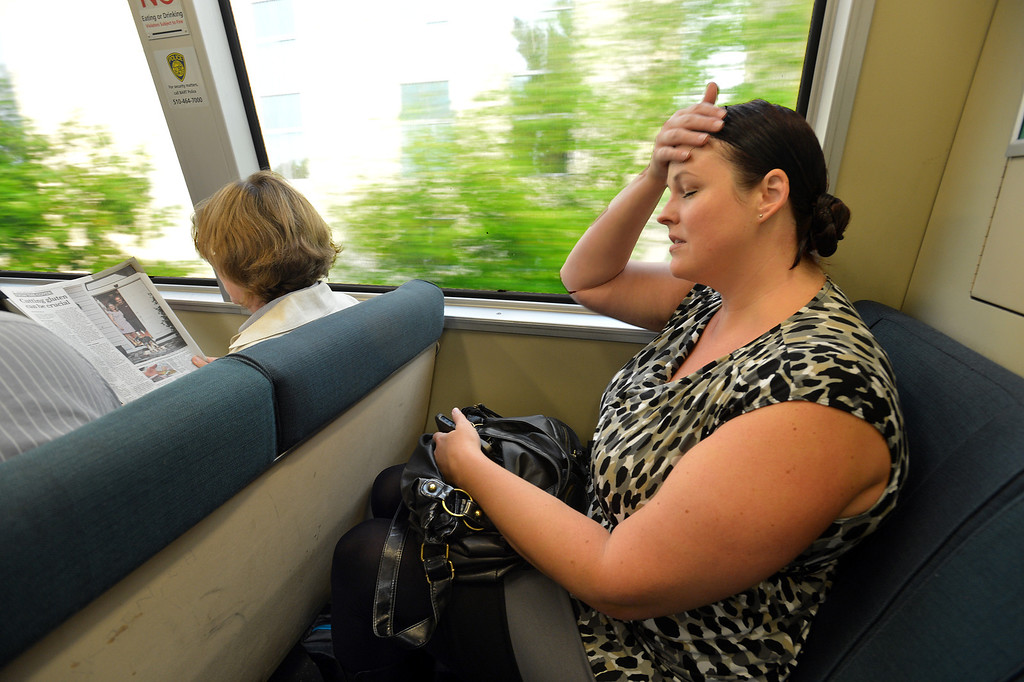 . Lori Myers, of Walnut Creek, rushes to the back of a BART train grabbing an empty seat as it leaves the Pleasant Hill BART station on her way to her job in San Francisco, where she will get off at the Embarcadero station, in Pleasant Hill, Calif., on Tuesday, July 20, 2013. Myers, a legal secretary by day and dance instructor by night, is one of many Bay Area commuters without the option to telecommute or take advantage of many ride-sharing options if BART goes out on strike. (Dan Rosenstrauch/Bay Area News Group)