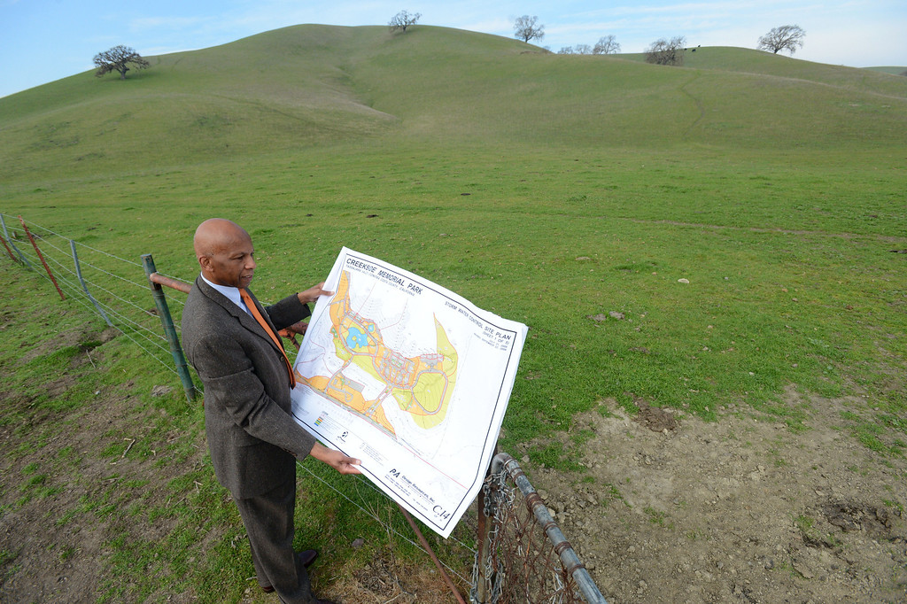 . Former Mayor of San Ramon H. Abram Wilson, of San Ramon, stands on the surrounding land and holds plans for the proposed Creekside Memorial Park Cemetery off Camino Tassajara in Contra Costa County, Calif., on Saturday, Feb. 2, 2013. Wilson has been an advocate for the cemetery for nearly a decade. However, there is opposition from environmental groups and neighbors. (Doug Duran/Staff)