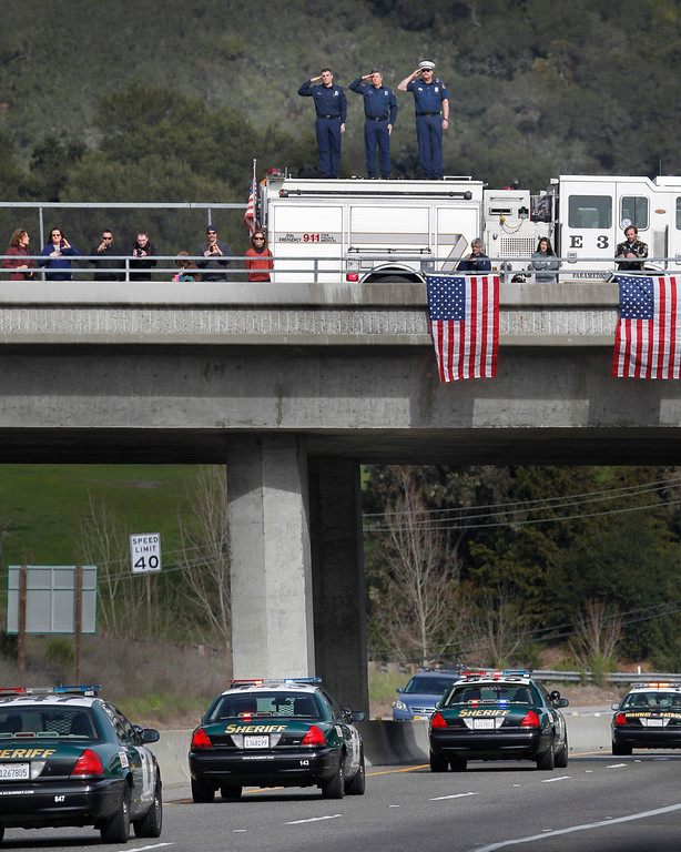". Santa Clara County firefighters, from left, Dave Sosine, Bruce Ingle and Capt. Dave Riggert, salute from atop their fire truck on the Bear Creek Road overpass as a procession of police officers from supporting agencies, coming from Santa Cruz, heads north on Highway 17 on their way to HP Pavilion in San Jose on Thursday, March 7, 2013. The procession was to the memorial service for Santa Cruz city police officers Loran ""Butch\"" Baker and Elizabeth Butler, shot to death on Feb. 26 when they followed up on a sexual assault investigation with an unstable man with a history of sexual assault.  (Patrick Tehan/Bay Area News Group)"