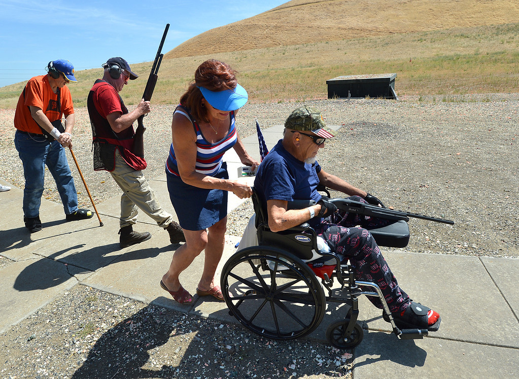 . Dorthy Bayer, of Antioch, helps wheel Earl Batterton, of San Jose, a U.S. Army Vietnam veteran, to the next target position during the George Findly Memorial Disabled Veteran Trap Shoot at the Bay Point Rod and Gun Club in Concord, Calif., on Saturday, June 15, 2013.  Each vet was assigned a mentor/coach from the club and each got to shoot two sets of flying clay targets.  (Dan Rosenstrauch/Bay Area News Group)