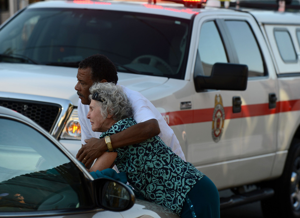 . Neighbor Leroy Crump consoles Patti Geyser as she looks over at her home smoldering in the 400 block of H Street  in Antioch, Calif.,  on Wednesday, March 13, 2013.  (Susan Tripp Pollard/Staff)