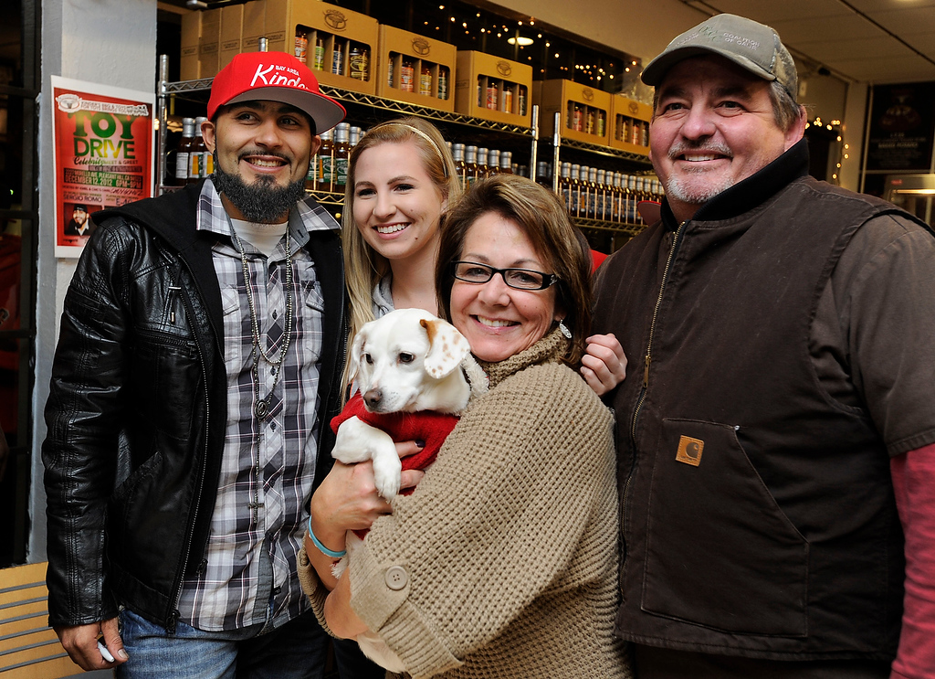 . Giants reliever Sergio Romo poses for a photograph with Emily Trebino, Cindy Trebino and Rich Trebino at Kinder\'s Meats and Deli on Wednesday, Dec. 12,  2012, in Pleasant Hill, Calif. Cindy holding Franklin, the family\'s rescued Jack Russell-dachshund mix. The Martinez family was hoping to make a Christmas card out of the photograph with the World Champion celebrity. (Susan Tripp Pollard/Staff)